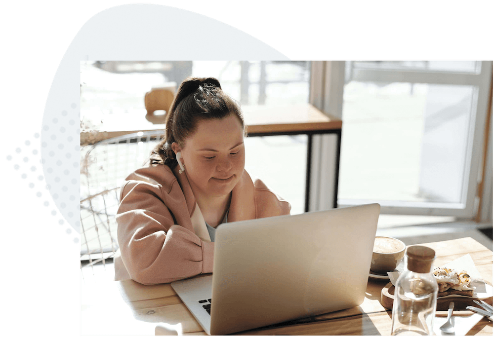 Adult girl with down syndrome talking on her laptop in virtual program